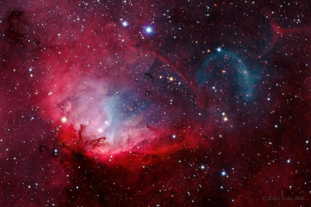 Nebulosa da Tulipa, na constelação de Cisne. Do lado direito nota-se um arco azulado causado por Cygnus-X1, um quasar.